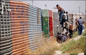 Illegal-immigrants-climbing-over-border-fence